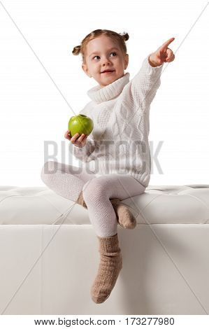 Little girl in a trendy knitted clothes holds apple, looking up and pointing your finger, isolated on white