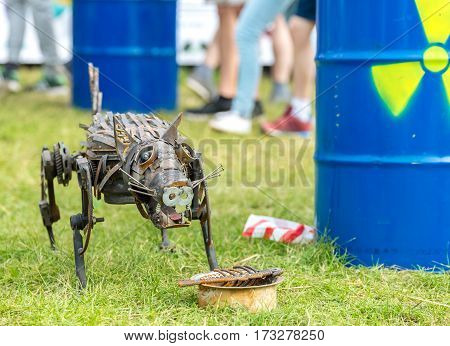 The metal statue dog on the russian festival and sign of radiation  on a barrel