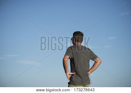 Man With Hands On Hips Viewed From Behind