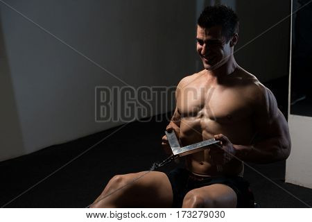 Young Man Doing Heavy Weight Exercise For Back