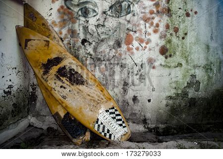 Two old surfboards lie stacked against a mouldy wall.