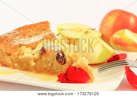 Baked apple pie on a white plate with a fork