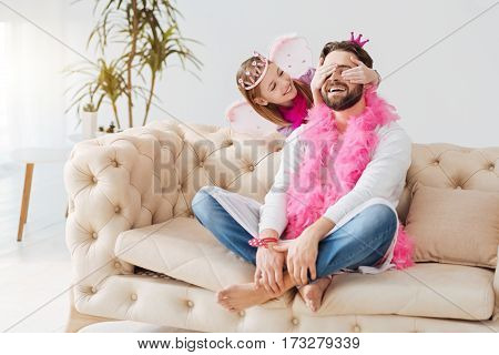 Just relax. Happy girl wearing pink feather around her neck keeping her hands on eyes of her father while looking at him
