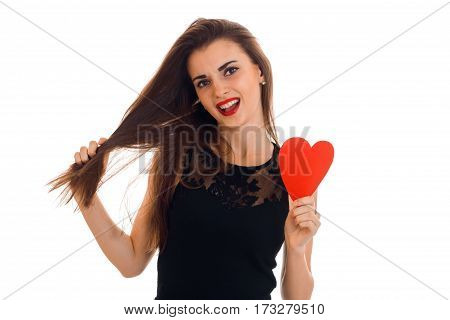 Beautiful girl with long hair holding a red heart isolated on white background.