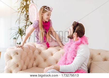 Have a break. Attractive girl wearing pink feather around her neck and wings keeping her hands on the back of coach while looking at father
