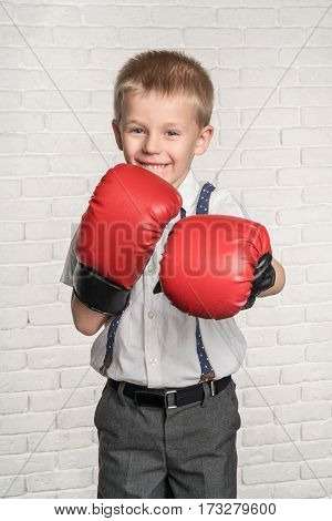 Little joyful boy in red boxing gloves about white brick wall