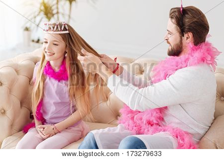 Beauty time. Handsome bearded man keeping pink feather around his neck wearing white jumper holding hair of his daughter in his hands