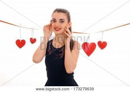 Young girl in a black dress stands near the ribbon with red hearts and smiling isolated on white background.