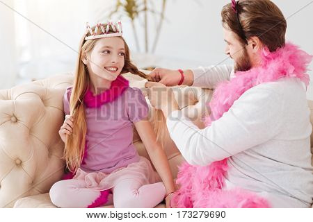 Time with pleasure. Handsome male person keeping pink feather around his neck wearing white jumper making braid to daughter