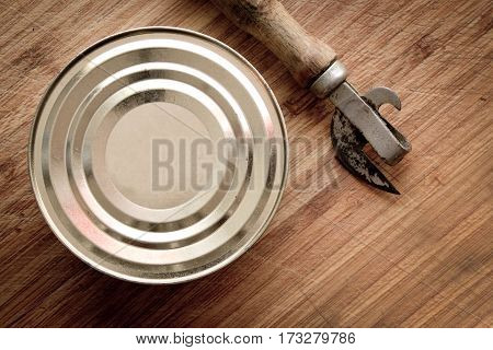 Tin Can And Can Opener On Wooden Background