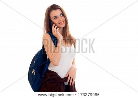 Cheerful young girl in white shirt and backpack talks on her cell phone isolated on white background.