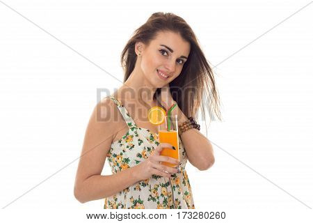 Smiling young girl holds in her hand a glass of orange juice is isolated on a white background