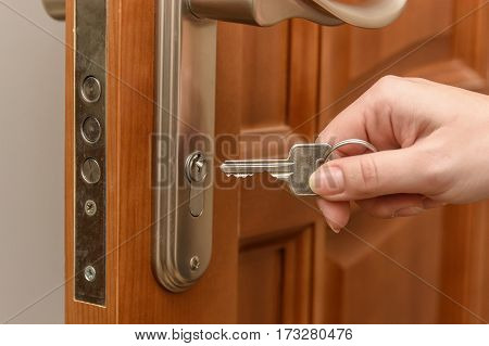Close up of woman's hand opening door with key.