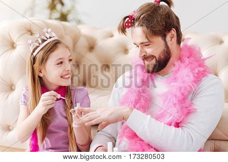 Do you like it. Smiling little girl keeping smile on her face holding brush in right hand while polishing nails