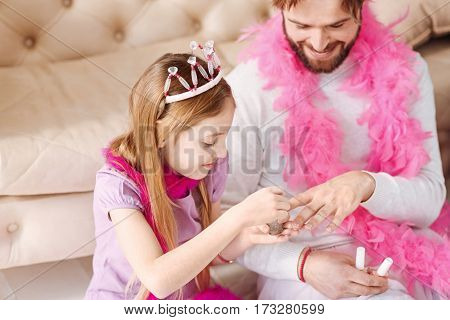 Our weekend. Serious girl wearing pink crown on her head holding nail polish in right hand while making manicure to her dad