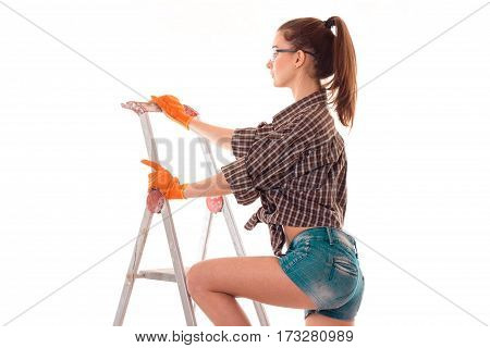 Young girl in plaid shirt and shorts on a ladder to repair isolated on white background.