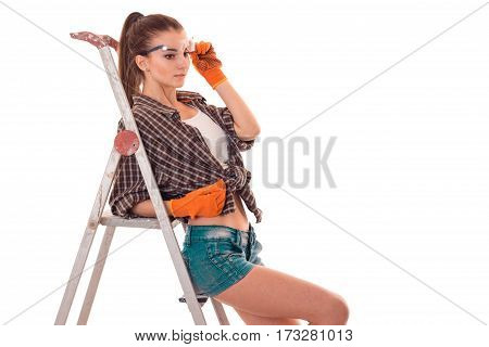Young sexy girl in plaid shirt and shorts leaning on a ladder is isolated on a white background.