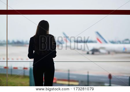 Woman With Hand Luggage In International Airport, Looking Through The Window At Planes