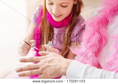 Be very attentive. Positive little female keeping smile on her face holding brush in right hand while painting male nails