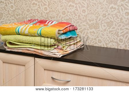 Home wardrobe with several towels lying on shelf