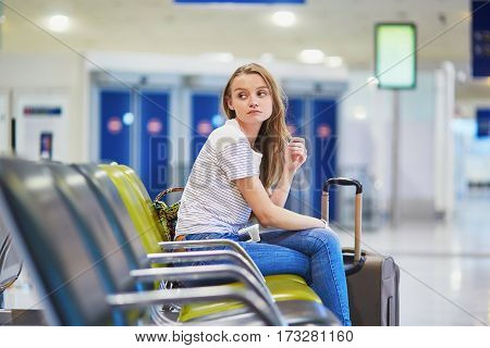 Tourist Girl In International Airport, Waiting For Her Flight, Looking Upset