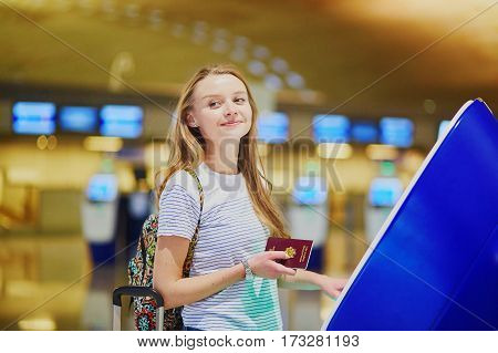 Tourist Girl With Backpack And Carry On Luggage In International Airport, Doing Self Check-in