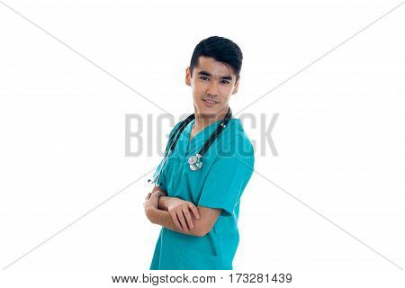Young doctor stands sideways with a stethoscope and keeps arms together isolated on white background.