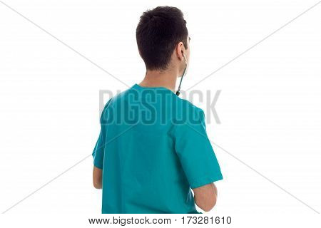 Young doctor in blue scrubs stands with back to camera isolated on white background.
