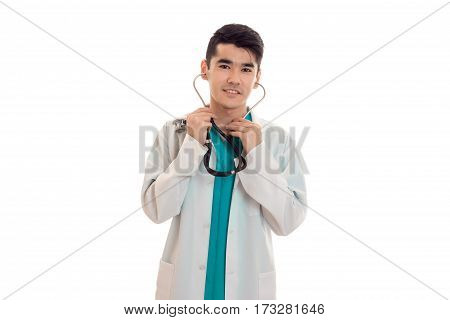 Young doctor in a white lab coat stands up straight with a stethoscope in his ears is isolated on a white background.