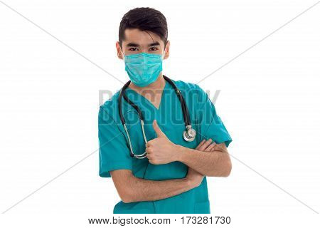 Young doctor with a surgical mask on his face and a stethoscope shows a class of isolated on white background
