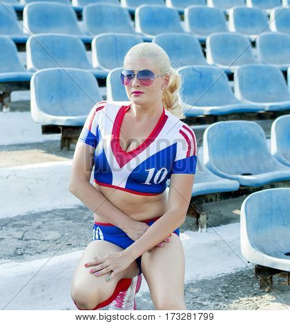 the beautiful sportswoman on a knee at stands of stadium a subject of the woman and sport