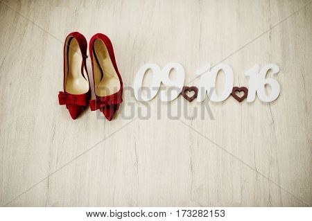 Red Velvet Bride Shoes On Wooden Background With Sign Of Date Wedding.
