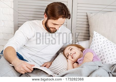 Please sleep. Happy bearded man keeping smile on his face lying near his daughter while holding book with tales
