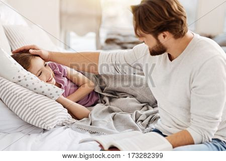 Good buy. Pretty girl lying under grey blanket holding her hands under head while looking on daddy