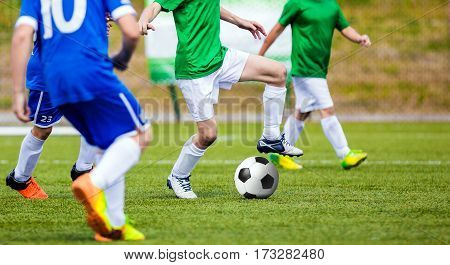 Young Soccer Players Kicking Match. Football Player Kicking Ball on the Pitch. Sport Competition Between Two Children Soccer Teams. Kids in Blue and Green Soccer Jersey Shirts