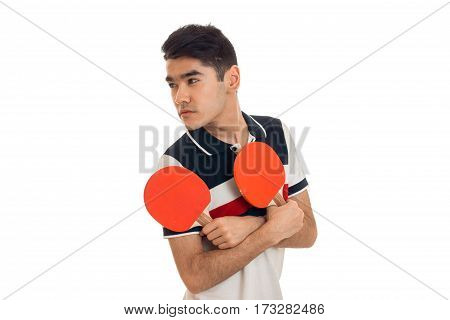 young guy looks away and holding rackets for table tennis is isolated on a white background