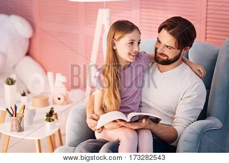 So please. Cunning bearded man wearing white jumper embracing his daughter while holding book in left hand