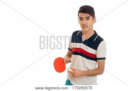 young guy looks straight and holding a racket for table tennis is isolated on a white background