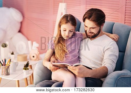 Time for book. Attractive girl wearing violet T-shirt embracing her daddy while reading book