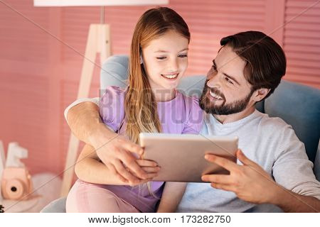 I can show you. Pretty little girl wearing violet tee shirt sitting on knees of her father while looking in tablet
