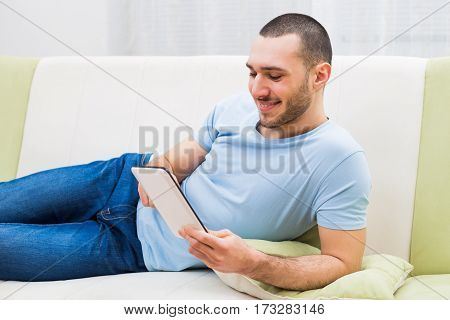 Man using digital tablet at his home.