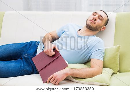 Man fell asleep with book at his home.
