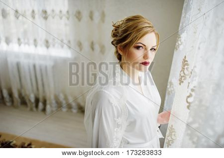 Blonde Bride In A Bathrobe On Wedding Day Near Curtains At Her Room.