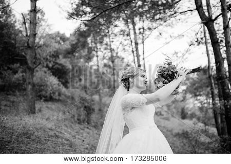 Blonde Bride With Wedding Bouquet And Bright Make Up At Autumn Pine Wood. Black And White Photo