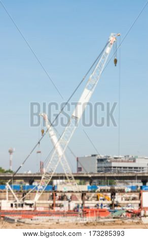 Double white crane is working in the large construction site near the urban area.(Blur focus)