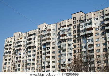 Large obsolete suburban apartment building in clear sunny day