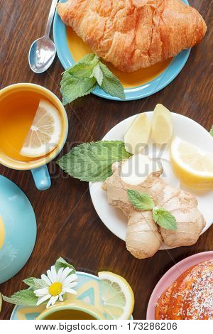 Cup of herbal tea with lemon and mint leaves ginger root and croissant on the wooden background top view