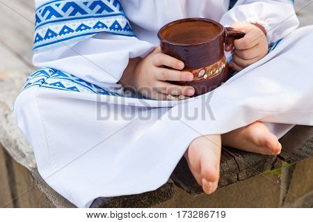Children's picnic with dairy products and pancakes. Children in the Russian national clothes on a picnic. Rural food. Food background. The child in national clothes holds in hand a clay mug with milk.