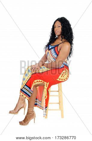 A pretty African American woman sitting in a colorful dress with long black curly hair isolated for white background.