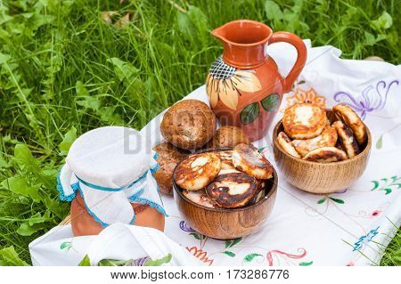 Dairy products on the embroidered white cloth. Cheesecake and milk on the table in an earthenware dish. Rural food. Food background. Picnic with dairy products and pancakes.